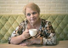 Femme agée avec la tasse de thé au café Image stock