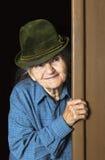 Femme agée avec le chapeau jetant un coup d'oeil par la porte à la maison Image stock