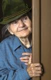 Femme agée avec le chapeau jetant un coup d'oeil par la porte à la maison Photo stock
