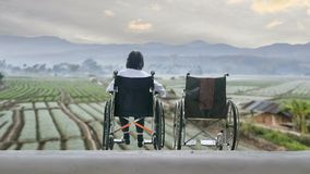 Femme agée avec le fauteuil roulant vide se tenant ensemble banque de vidéos