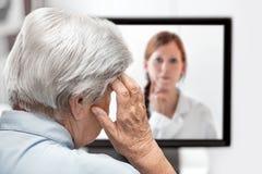 Femme agée avec le mal de tête, docteur sur le moniteur écoutant, Co Photos stock