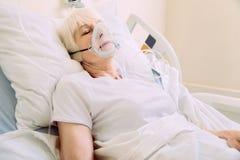 Femme agée avec le masque à oxygène se situant dans le lit d'hôpital Photo libre de droits