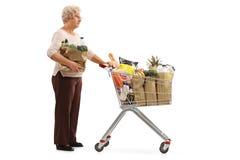 Femme agée avec le sac et caddie attendant dans la ligne Image libre de droits