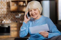 Femme agée avec plaisir faisant un appel téléphonique Photographie stock