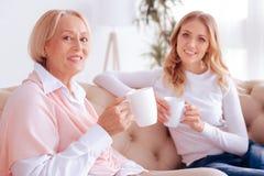 Femme agée avec plaisir tenant une tasse de thé Photos stock