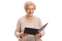 Femme agée avec un sourire de livre Images stock