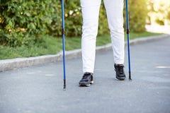Femme agée ayant une promenade avec dépister des bâtons Image libre de droits