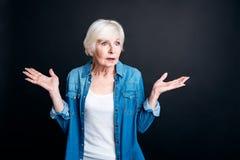 Femme agée confuse se tenant sur le fond noir photographie stock