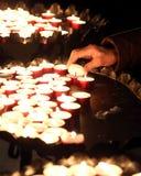 Femme agée dans la prière et allumée une bougie Image stock