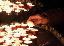Femme agée dans la prière et allumée une bougie Image libre de droits