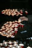 Femme agée dans la prière et allumée une bougie dans l'église Images libres de droits