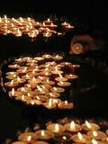 Femme agée dans la prière et allumée une bougie dans l'église Photo stock