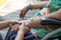 Femme agée dans le fauteuil roulant tenant des mains avec le travailleur social Photographie stock libre de droits