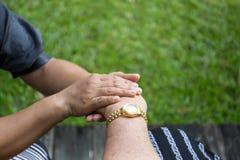 Femme agée dans le fauteuil roulant tenant des mains avec le travailleur social Images stock