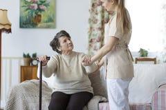 Femme agée de aide d'infirmière à se lever Photographie stock libre de droits
