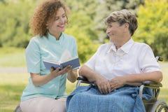 Femme agée de lecture d'infirmière dans un jardin Image stock