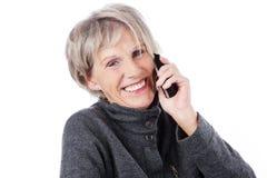 Femme agée de sourire au téléphone Photos libres de droits