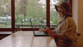 Femme agée de sourire avec l'ordinateur portable banque de vidéos