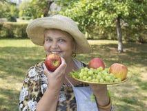 Femme agée de sourire dans le pays avec des pommes Photographie stock libre de droits