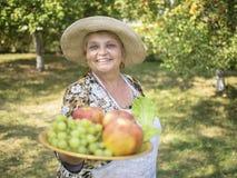 Femme agée de sourire dans le pays montrant des pommes et des raisins du plat Photographie stock