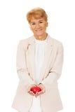 Femme agée de sourire tenant le modèle de coeur Image libre de droits