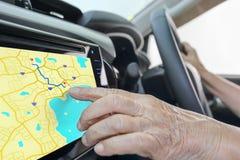 Femme agée employant le système de navigation de GPS dans la voiture Image libre de droits
