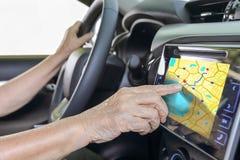 Femme agée employant le système de navigation de GPS dans la voiture Image stock