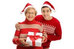 Femme agée et jeune homme utilisant des chapeaux de Santa avec des RP de Noël Image libre de droits