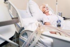 Femme agée faible respirant avec l'unité respirating artificielle Photos stock