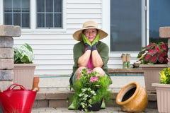 Femme agée faisant une pause tandis que mise en pot vers le haut des usines Photographie stock