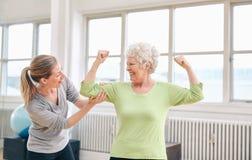 Femme agée fière fléchissant son biceps avec l'entraîneur personnel Image libre de droits