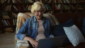 Femme agée gaie communiquant par l'Internet clips vidéos