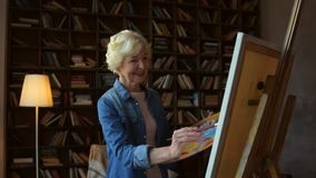 Femme agée gaie dessinant à la maison clips vidéos