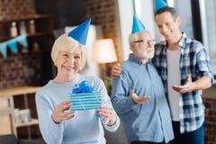 Femme agée gaie posant avec un cadeau d'anniversaire Image stock