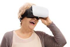 Femme agée heureuse à l'aide d'un casque de VR Photographie stock
