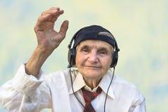 Femme agée heureuse avec des écouteurs écoutant la musique photo stock