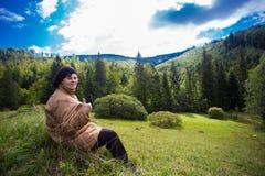 Femme agée heureuse avec des pouces se reposant sur la colline en montagne Photographie stock libre de droits