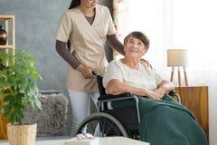 Femme agée heureuse dans le fauteuil roulant Photographie stock libre de droits