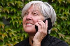 Femme agée heureuse de sourire parlant dehors à un téléphone portable avec les feuilles d'automne intéressantes photos stock