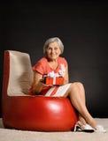 Femme agée heureuse s'asseyant avec le cadeau Image libre de droits