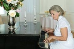 Femme agée jouant le piano à la maison Photo libre de droits