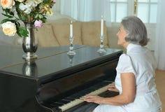Femme agée jouant le piano à la maison Images libres de droits