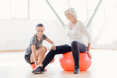 Femme agée joyeuse s'asseyant sur la boule de forme physique Photo stock