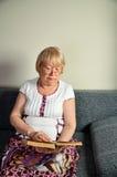 Femme agée lisant un livre se reposant sur la verticale de divan Photos stock