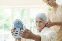 Femme agée malade avec le foulard et travailleur social regardant dans le miroir photos stock