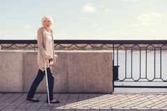 Femme agée marchant le long du pont sur des béquilles Photos stock