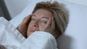 Femme agée massant la tête dans le lit, souffrant de la migraine, désordre de mal de tête banque de vidéos