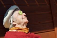 Femme agée mettant des concombres sur vos yeux images stock
