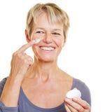 Femme agée mettant des soins de la peau image stock
