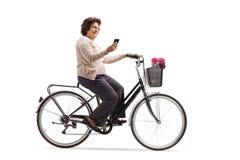 Femme agée montant une bicyclette et regardant son téléphone photos stock